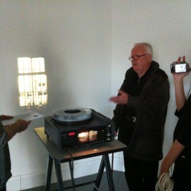 """Collectiebeheerder Louis Baltussen en Jan Dibbets bij de dia-projectie voor """"The Shortest Day at the Van Abbemuseum"""" (1970), gefilmd door Marleen Wagenaar, in het Van Abbemuseum, Eindhoven, 11 november 2011 (foto: Sanneke Stigter)."""